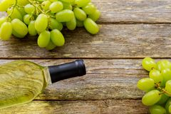 Bunch of grapes and wine bottle on wooden table background with copy space. Bunch grapes and wine bottle on wooden table background with copy space stock photography