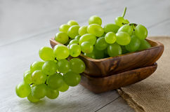 Bunch of grapes in a wooden bowl. Bunch of grapes on wooden background Stock Image