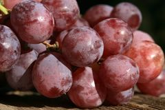 Bunch of grapes on a wooden table Stock Photos