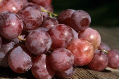 Bunch of grapes on a wooden table stock image