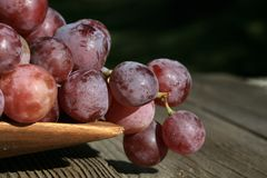 Bunch of grapes on a wooden table an old, country house. stock photo