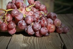 Bunch of grapes on a wooden table an old, country house. royalty free stock photos