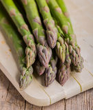 Bunch of green asparagus on cutting board. And wooden background Royalty Free Stock Photo