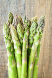 Bunch of green asparagus. Bunch of fresh green asparagus in front of timber wall Royalty Free Stock Image