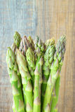 Bunch of green asparagus. Bunch of fresh green asparagus in front of timber wall Royalty Free Stock Photo