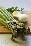 Bunch of green asparagus with eggs royalty free stock photography