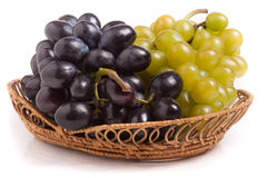 Bunch of green and blue grapes in wicker basket isolated on white background stock photo