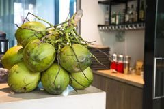 A bunch of green coconuts on a table on the background. Of kitchen restaurant equipment Stock Image