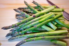Bunch of green fresh asparagus or spargel in german on the choping plate with kitchen knife Royalty Free Stock Photos