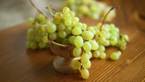 Bunch of green grapes on a dark wooden table. Close-up stock video footage