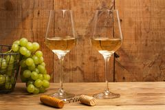 Green grapes and white wine glasses. Bunch of green grapes and white wine glasses royalty free stock image