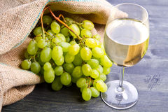 Bunch green grapes and wine on wooden background Stock Photo