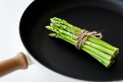 Bunch of green mini asparagus in a pan. White background, top view, space for text. stock photo