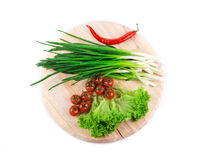 Bunch of green onion on wooden platter. Royalty Free Stock Images
