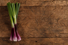 Bunch of green onions. Bunch of green spring onions on rustic wooden background, left side Stock Photo