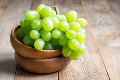 Bunch of green ripe grapes in wooden bowl, copy space Stock Photo