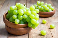 Bunch of green ripe grapes in a wooden bowl Royalty Free Stock Images
