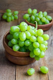 Bunch of green ripe grapes in a wooden bowl Stock Image