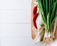 Bunch of green young scallions with roots on a white background of old wooden boards vintage top view, healthy diet food stock photo