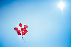 Bunch of group red balloons on a blue sky Stock Photos