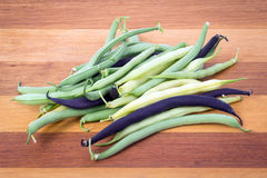 Bunch of harvested bean three varieties on table. Bunch of harvested bean Purple, green and yellow Wax Snap Beans Royalty Free Stock Images