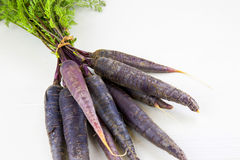 Bunch of heirloom purple carrots, over white and wooden backgrou Royalty Free Stock Image