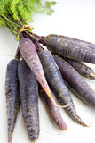 Bunch of heirloom purple carrots, over white and wooden backgrou Stock Photos