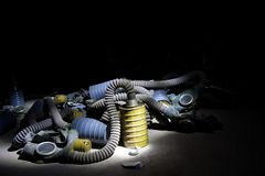 A bunch of hoses, gas masks and filters in dark room royalty free stock image
