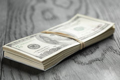 Bunch of hundred dollar notes tied with rubberband. On wood table, shallow focus Royalty Free Stock Photo