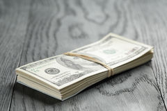 Bunch of hundred dollar notes tied with rubberband. On wood table, shallow focus Royalty Free Stock Photography