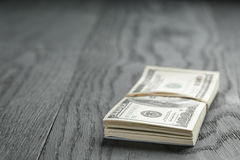 Bunch of hundred dollar notes tied with rubberband. On wood table, shallow focus Royalty Free Stock Image