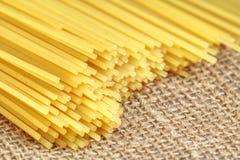 Bunch of Italian spaghetti closeup. Yellow long spaghetti on a rustic background Stock Photos