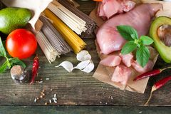 Bunch of Italian spaghetti, noodles soba and sommel, chicken raw meat, avocado with tomato on an old wooden background. Bunch of Italian spaghetti, raw soba Stock Images