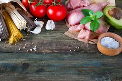 Bunch of Italian spaghetti, noodles soba and sommel, chicken raw meat, avocado with tomato on an old wooden background. Bunch of Italian spaghetti, raw soba Stock Photos