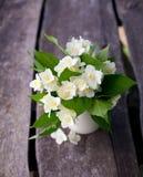 Bunch of jasmine flowers on wooden garden table Stock Photos