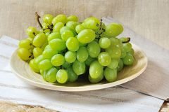 Bunch of juicy green grapes on a wooden plate Royalty Free Stock Photography