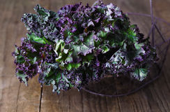 Bunch of kale on a rustic wooden background. Bunch of organic kale in a woven basket on a rustic wooden background. Selective focus, shallow dof royalty free stock photo