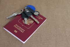 Bunch of keys and the international passport of the Russian Federation. On a brown background with copy space Royalty Free Stock Photo