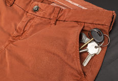 Bunch of keys sticking out of his trouser pocket that are on the table Royalty Free Stock Photography