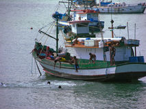 Bunch of kids diving from fishing boat Stock Images