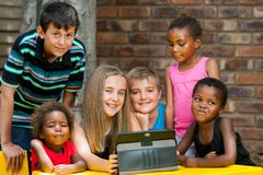 Bunch of kids playing on tablet. Stock Photo