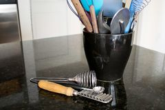 A bunch of kitchen utensils on a counter. Several kitchen utensils stuffed in a black ceramic container on a black granite counter with some utensils on the royalty free stock image