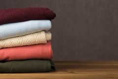 Bunch of knitted warm sweaters with different knitting patterns folded in stack on brown wooden table royalty free stock photo