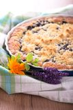 Bunch of lavender blooms and marigold in front of berry pie stock photo