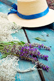 Bunch of lavender flowers, fishing net and straw hat on the blue vintage wood background. Selective focus, vertical.  Royalty Free Stock Images