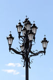 A post of lights with a cross. On one lamppost nine lamps of retro style with a cross at the top. Lights are located near the Church Royalty Free Stock Image