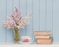Bunch of lilac, books and teacup. Gentle bunch of lilac, vintage books and china teacup on the table on blue wooden background Stock Photography