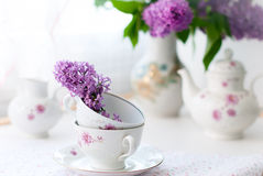 Bunch lilac flowers in a bowl. White tea set, a bouquet of lilac in a vase and a sprig of lilac in a cup Royalty Free Stock Photos