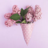 Bunch of lilac flowers in paper cone on purple background from above, flat lay stock image