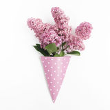 Bunch of lilac flowers in paper cone on white background from above, flat lay stock photos